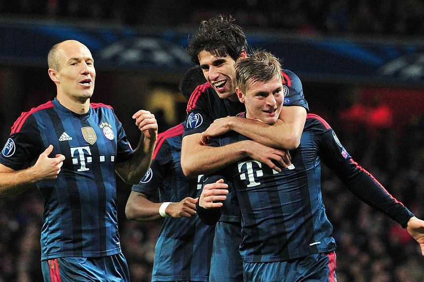 Bayern Munich's midfielder Toni Kroos (right) celebrates after scoring his team's first goal during the Uefa Champions League Last 16, first leg football match between Arsenal and Bayern Munich at The Emirates Stadium in north London on Feb 19, 2014.