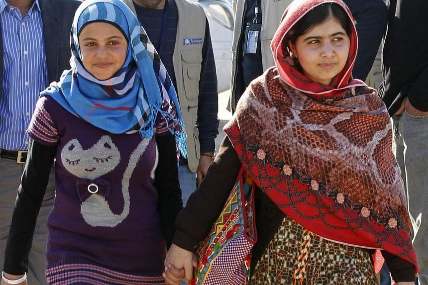 Pakistani schoolgirl Malala Yousafzai (right), who survived being shot in the head by the Taleban, walks alongside Syrian refugee Mazoon Rakan after attending a press conference at the Zaatri refugee camp, near the Jordanian border with Syria, on Feb
