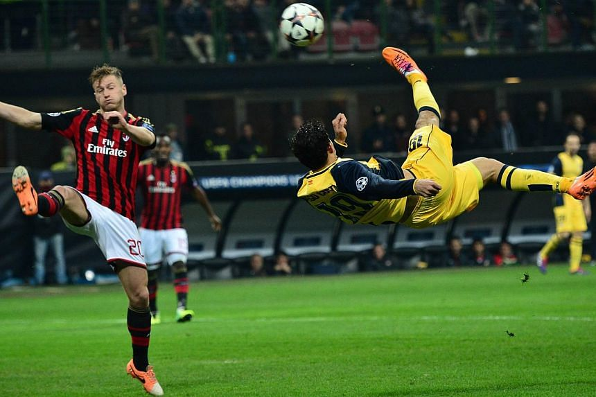 Atletico Madrid's Brazilian forward Diego da Silva Costa (right) makes a bicycle kick during the Champions League match between AC Milan and Atletico Madrid, on Feb 19, 2014 at San Siro Stadium in Milan. He headed home much later in the game to seal