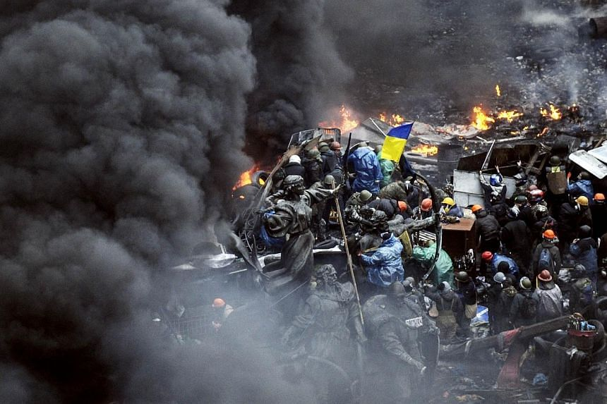 Protesters stand behind burning barricades during a face-off against police on Feb 20, 2014 in Kiev. -- PHOTO: AFP