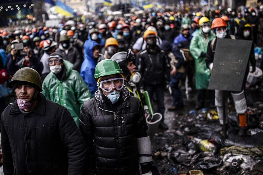 Protesters stand behind barricades during a face-off against police on Feb 20, 2014 in Kiev. -- PHOTO: AFP