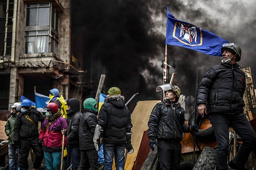 Protesters stand on barricades during clashes with police on Feb 20, 2014 in Kiev. -- PHOTO: AFP