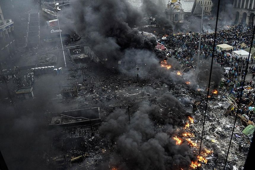 Protesters stand behind burning barricades during a face-off against police on Feb 20, 2014 in Kiev.Ukrainian protesters seized back Kiev's Independence Square in fresh clashes with riot police on Thursday, Feb 20, 2014, that left several injur