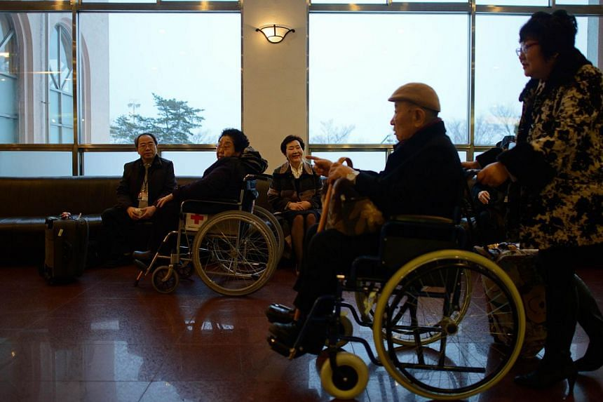 Participants of North and South family reunions pass through the lobby of their hotel as they prepare to depart for the North Korean border, in the eastern port city of Sokcho early on Feb 20, 2014. -- PHOTO: AFP