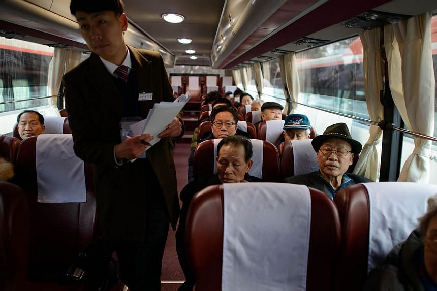 Participants of North and South family reunions sit aboard a bus prior to departing for the North Korean border, in the eastern port city of Sokcho early on Feb 20, 2014. -- PHOTO: AFP