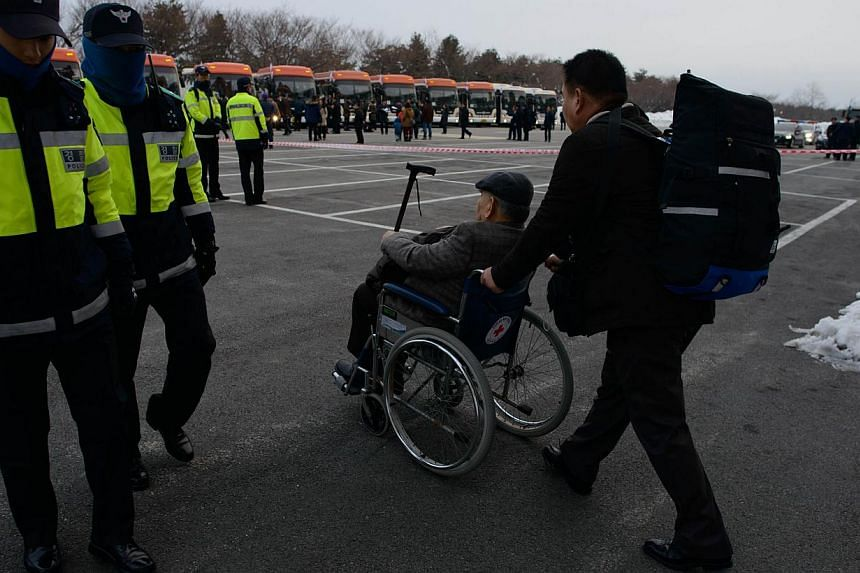 A man in a wheelchair is pushed towards a waiting bus preparing to depart for joint North and South Korean family reunions, in the eastern port city of Sokcho on Feb 20, 2014. -- PHOTO: AFP