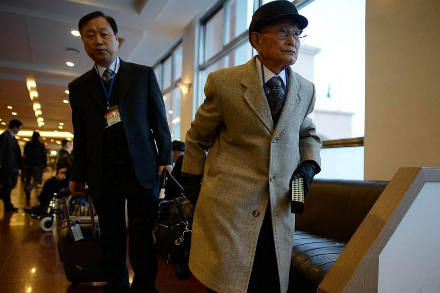 A participant (right) of North and South family reunions leaves the lobby of his hotel prior to departing for the North Korean border, in the eastern port city of Sokcho early on Feb 20, 2014. -- PHOTO: AFP