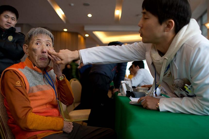 Lee Hyo Kuk (left) is checked by medical staff after arriving at the Hanwha resort as South Koreans selected to attend family reunions with the North gather in the eastern port city of Sockcho on Feb 19, 2014. -- PHOTO: AFP