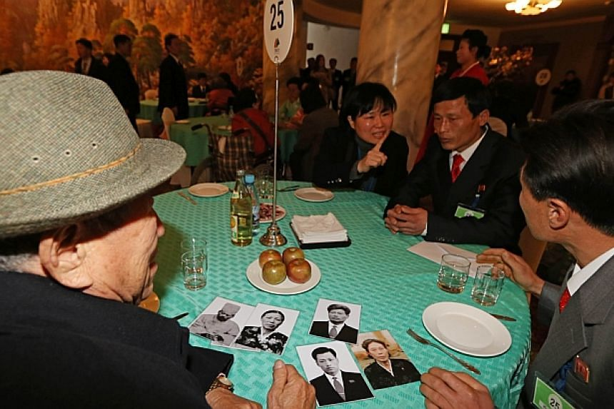 Na Bok Seop (left) of South Korea looks at photos as he sits with his nephew Na Ki Jun (right) of North Korea during a reunion event for families divided by the two countries, at the North Korean resort area of Mount Kumgang on Feb 20, 2014. -- PHOTO