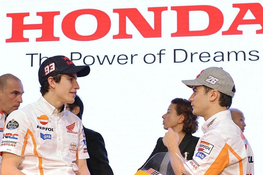 MotoGP Repsol Honda Team's Spanish Grand Prix motorcycle road racers, current MotoGP world champion Marc Marquez (front left) and Dani Pedrosa (front right) speak each other after a press conference in Tokyo on Feb 7, 2014. MotoGP world champion