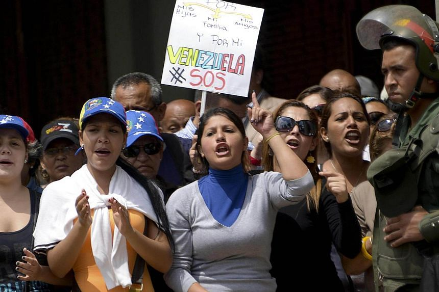 Supporters of Venezuelan opposition leader Leopoldo Lopez rallying on Wednesday, Feb 19, 2014, outside a Caracas court where he was expected to hear charges blaming him for a deadly episode of violence. -- PHOTO: AFP