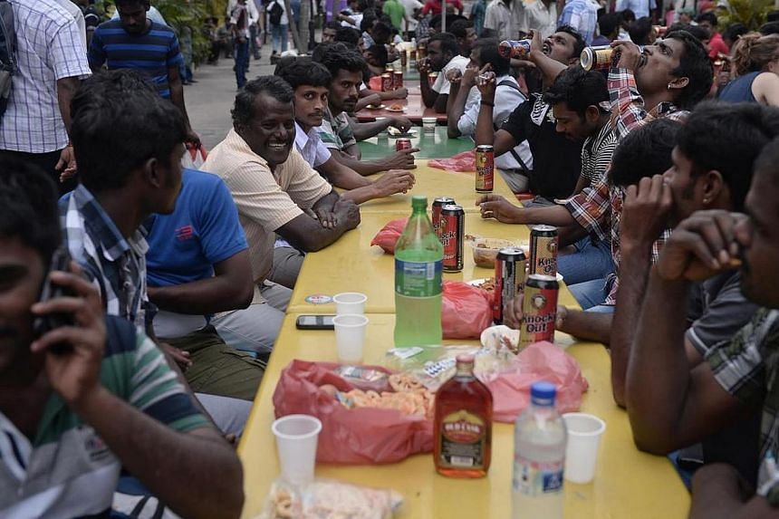 Foreign workers relaxing over liquor at a beer garden in Little India on Dec 22 last year. More foreign workers tanked up on alcohol have been making a nuisance of themselves by vomiting and even urinating in the private buses that take them from Lit