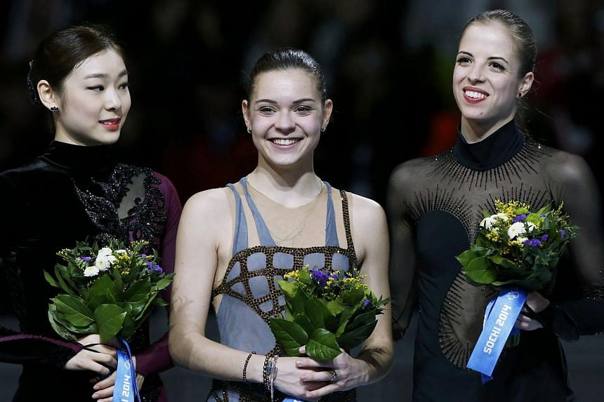 Russia's Adelina Sotnikova (centre), South Korea's Kim Yu Na (left) and Italy's Carolina Kostner stand together during the flower ceremony at the Figure Skating Women's free skating Program at the Sochi 2014 Winter Olympics, on Feb 20, 2014. -- PHOTO