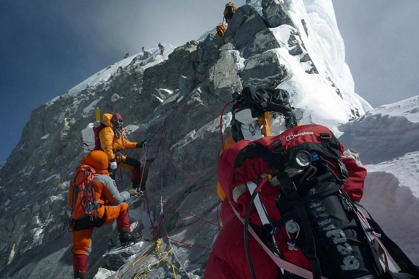 Unidentified mountaineers walk past the Hillary Step while pushing for the summit of Mount Everest as they climb the south face from Nepal on May 19, 2009. Nepal will enforce tighter controls of climbers on Mount Everest to ensure the world's highest