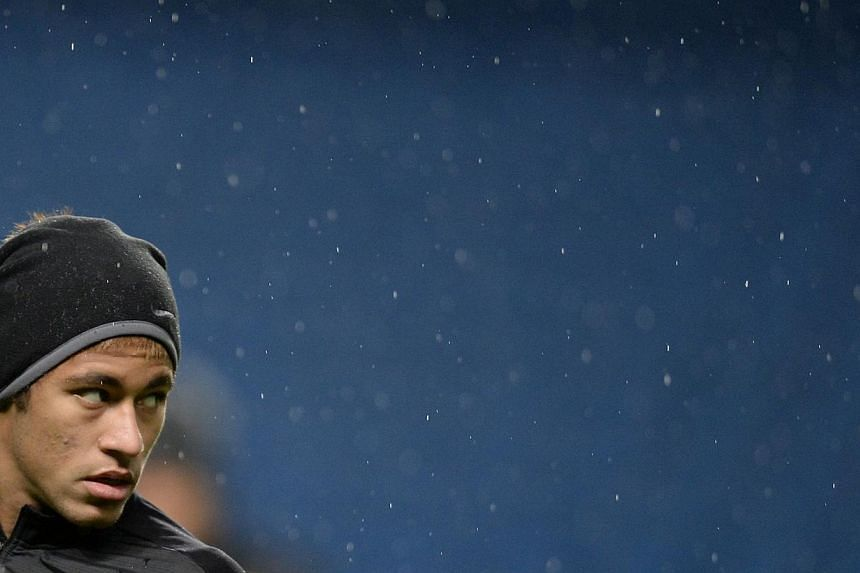 Barcelona's Neymar stands in the rain during a training session at the Etihad Stadium in Manchester, northern England, on Feb 17, 2014. A judge indicted Spanish football champions Barcelona on Thursday over alleged tax crimes linked to their signing