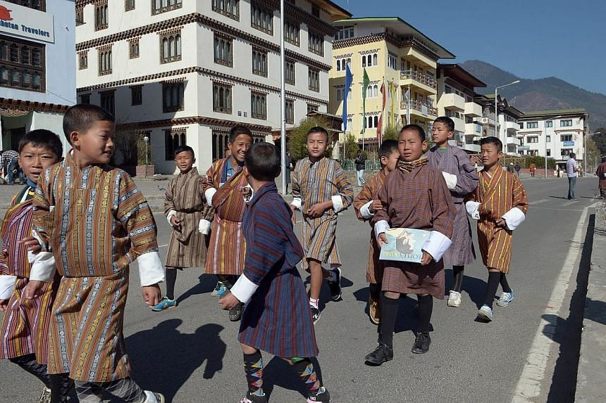 Bhutanese children walk together as they proceed to celebrations marking the Bhutanese King Jigme Khesar Namgyel Wangchuck's 34th birthday at the National stadium in Thimphu on Feb 21, 2014. -- PHOTO: AFP