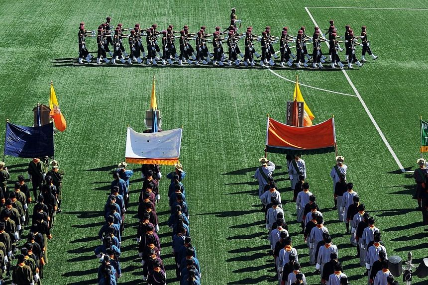 Royal Bhutanese bodyguards march past students as they participate in celebrations marking the Bhutanese King Jigme Khesar Namgyel Wangchuck's 34th birthday at the National stadium in Thimphu on Feb 21, 2014. -- PHOTO: AFP