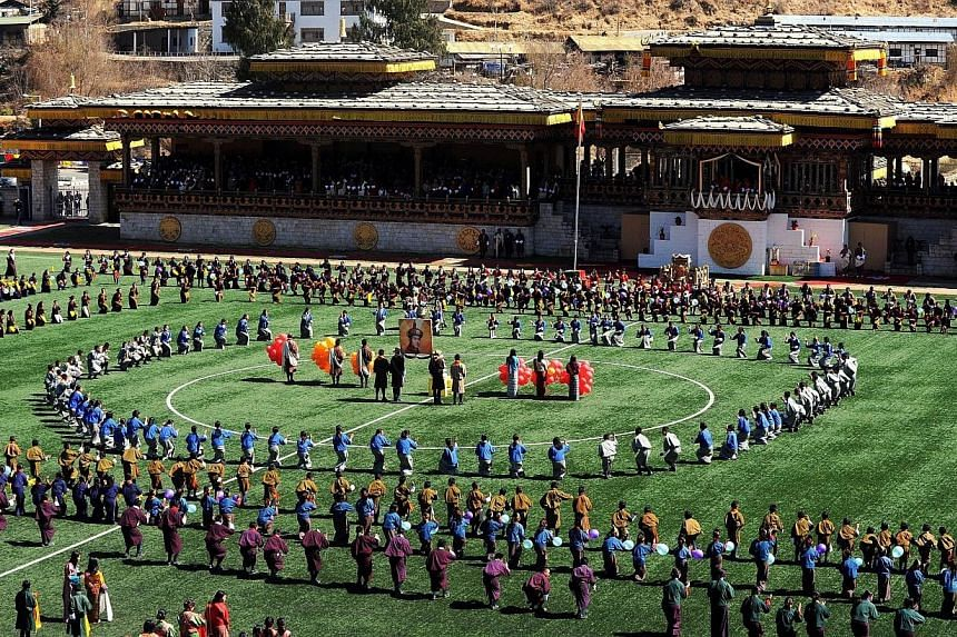 Bhutanese students participate in celebrations marking the Bhutanese King Jigme Khesar Namgyel Wangchuck's 34th birthday at the National stadium in Thimphu on Feb 21, 2014. -- PHOTO: AFP