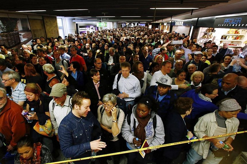 Hundreds of flight passengers wait past closed security gates during a strike in Frankfurt airport, Feb 21, 2014. -- PHOTO: REUTERS