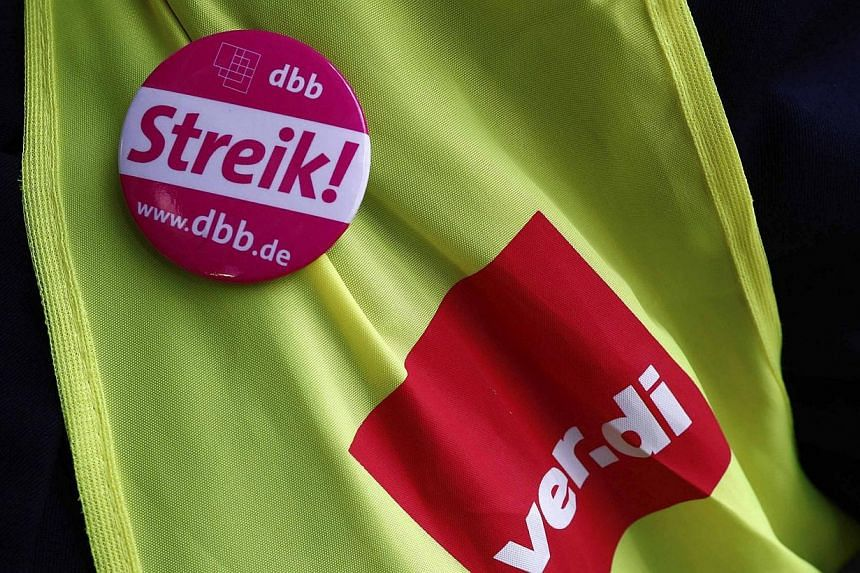 """A worker wearing a Union Verdi vest and a badge that reads """"strike"""" demonstrates in Frankfurt, Feb 21, 2014. -- PHOTO: REUTERS"""