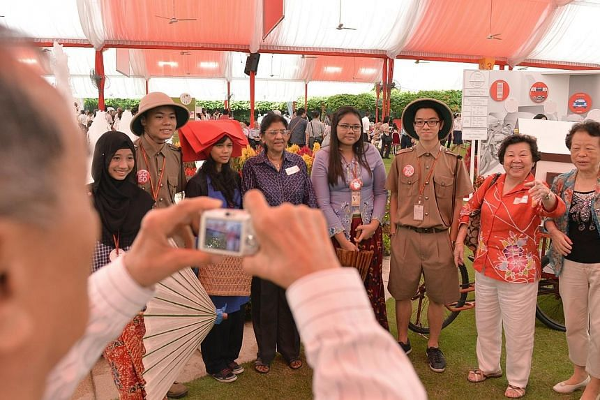 Guests at the Pioneer Generation Tribute event at the Istana on Feb 9, 2014, take pictures with people dressed as pioneers from early Singapore. The much-anticipated package for Singapore's pioneer generation will give this group assistance with thei