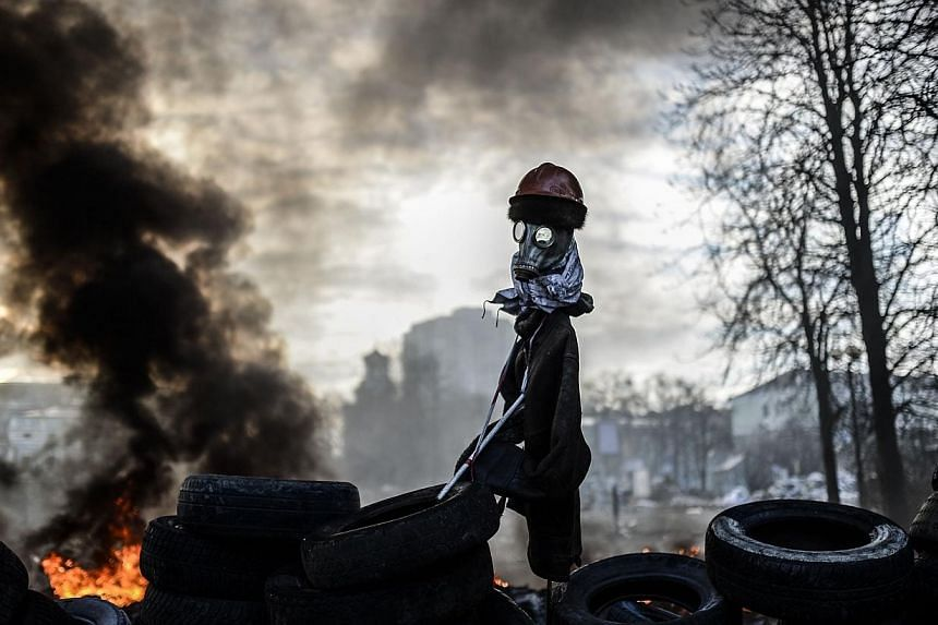 A scarecrow like mock anti-government protestor is pictured on a barricade between protestors and government forces on Feb 21, 2014 in Kiev. -- PHOTO: AFP