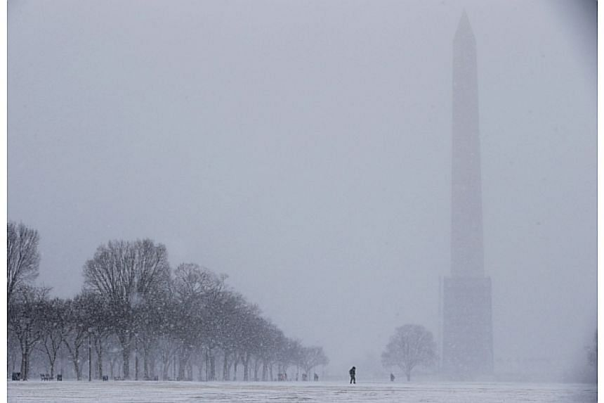 The Washington Monument fades into blowing snow on the National Mall, Jan 21, 2014 in Washington, DC. -- FILE PHOTO: AFP