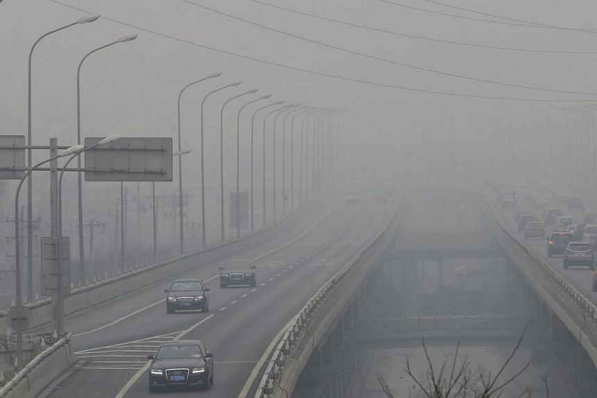 Cars drive on an overhead road amid the heavy haze in Beijing, Feb 21, 2014. -- PHOTO: REUTERS