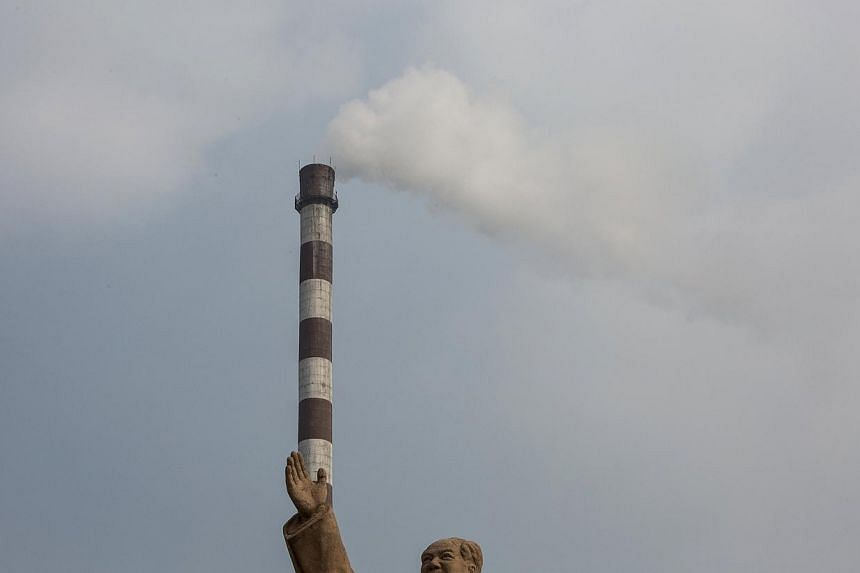 A statue of former Chinese leader Mao Zedong is seen in front of smoking chimney at a petrochemical plant in Nanjing, Jiangsu province, Feb 20, 2014. -- PHOTO: REUTERS