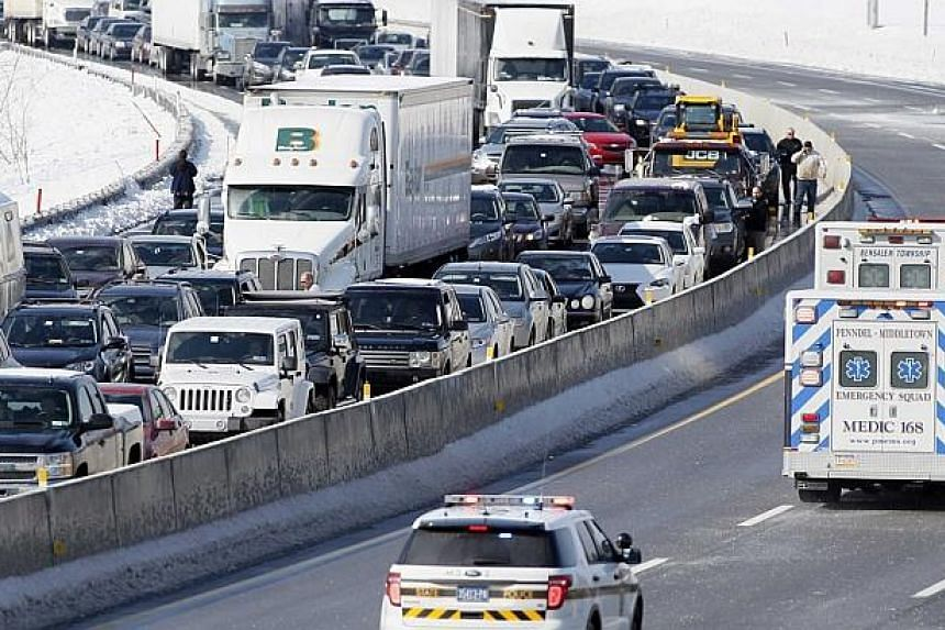 Drivers stand outside of their cars in the east bound lanes in this view looking west of Interstate 276, the Pennsylvania Turnpike, as emergency vehicles pass following a multi-car and truck accident near the Bensalem interchange. -- FILE PHOTO: REUT