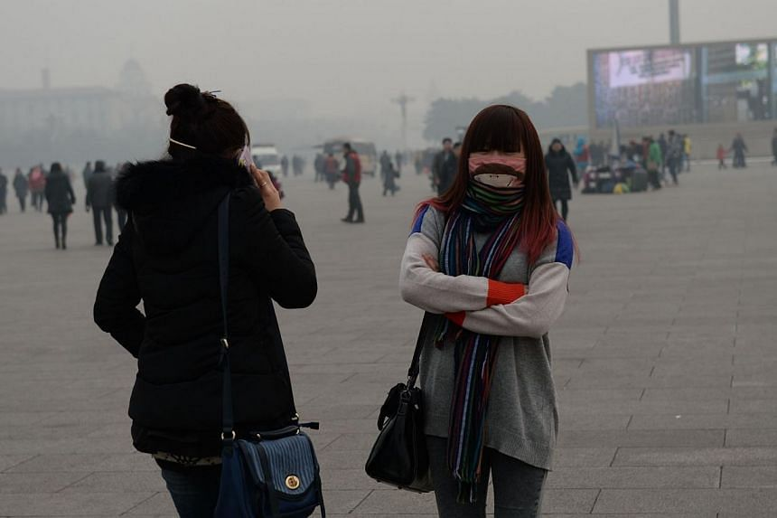 This picture taken on Feb 15, 2014, shows visitors covering their faces as they visit Tiananmen Square in Beijing. -- FILE PHOTO: AFP