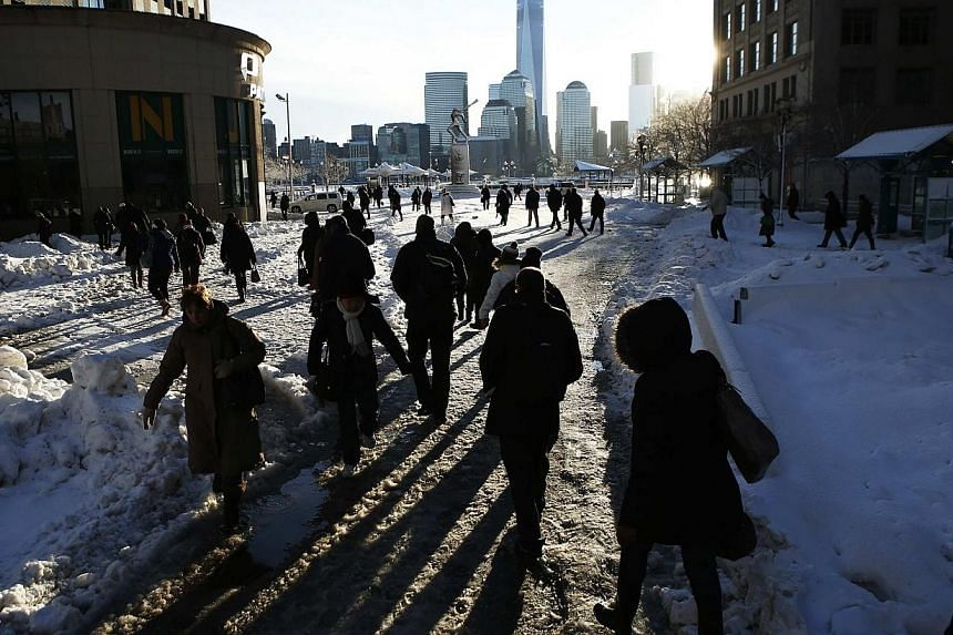 The New York skyline and the One World Trade Center are seen in the distance as people make their commute after a night of snow from Exchange Place in New Jersey to New York City, Feb 14, 2014. -- FILE PHOTO: REUTERS