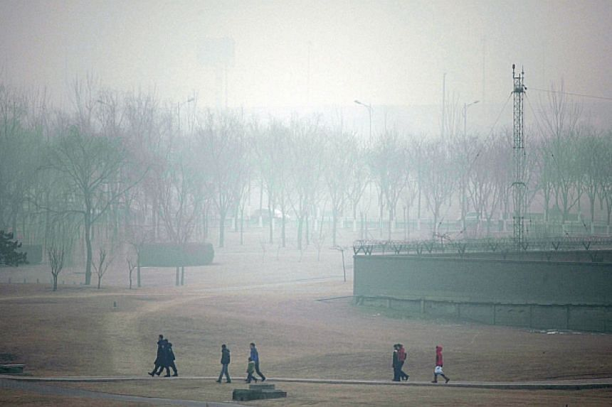 This picture taken on Feb 15, 2014, shows people walking along a path by the haze-covered Beijing Capital International airport, in Beijing. -- FILE PHOTO: AFP