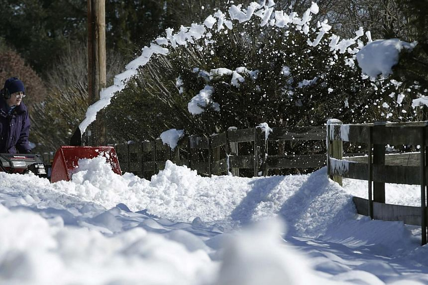 Nancy McIntosh clears her driveway of deep snow in Dayton, Maryland, Feb 14, 2014. -- FILE PHOTO: REUTERS