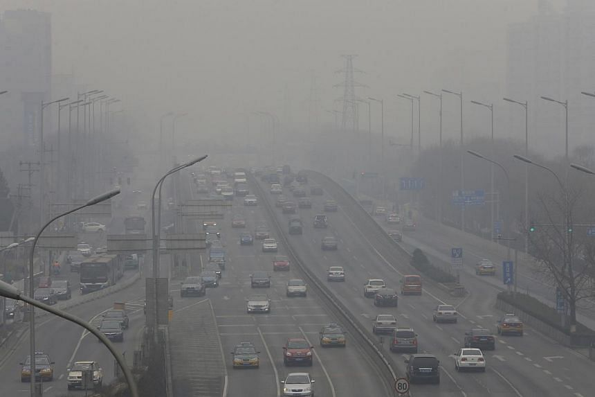 Cars drive on the second ring road amid the heavy haze in Beijing February 21, 2014. China's capital Beijing issued an emergency pollution alert for the first time on Thursday, Feb 20, 2014, warning residents to reduce outdoor activities and construc