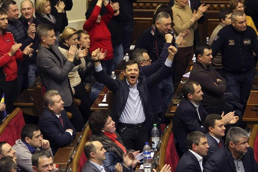Ukrainian opposition members celebrate during the voting in parliament in Kiev, Feb 20, 2014.Ukraine's president said on Friday, Feb 21, 2014, a deal had been clinched to end a three-month-old standoff with opposition protesters after the worst