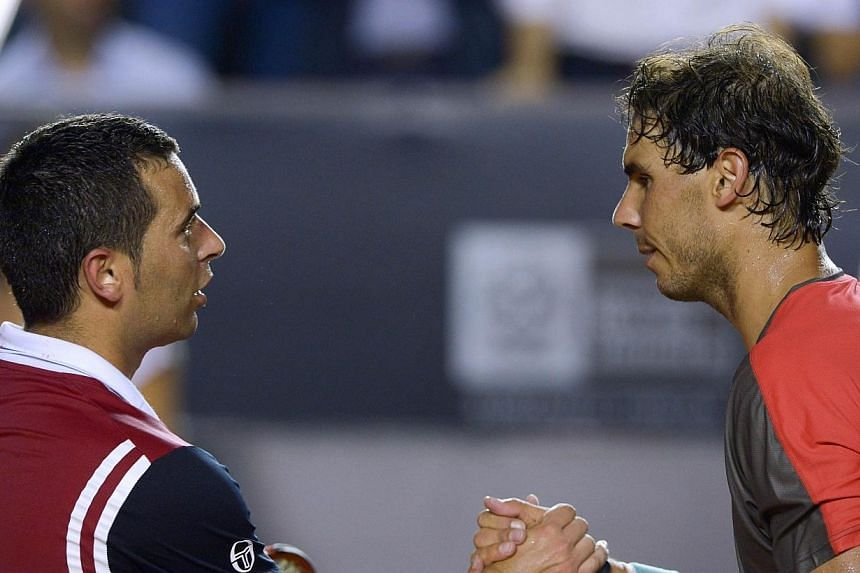 Rafael Nadal (right) of Spain shakes hands with Albert Montanes of Spain after the 2014 Rio Open men's singles tennis match in Rio de Janeiro, Brazil, on Thursday, Feb 20, 2014.Tennis world No. 1 Rafael Nadal breezed into the quarter-finals of