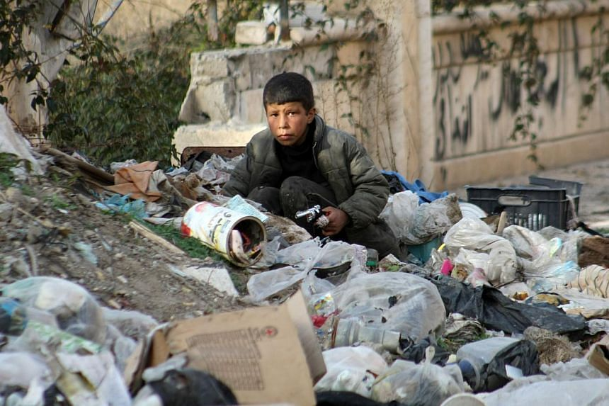 A young boy searches for food amid the garbage in the eastern Syrian town of Deir Ezzor on Feb 19, 2014. The United Nations Security Council will vote on Saturday on a draft resolution calling for immediate and unhindered humanitarian aid access in w