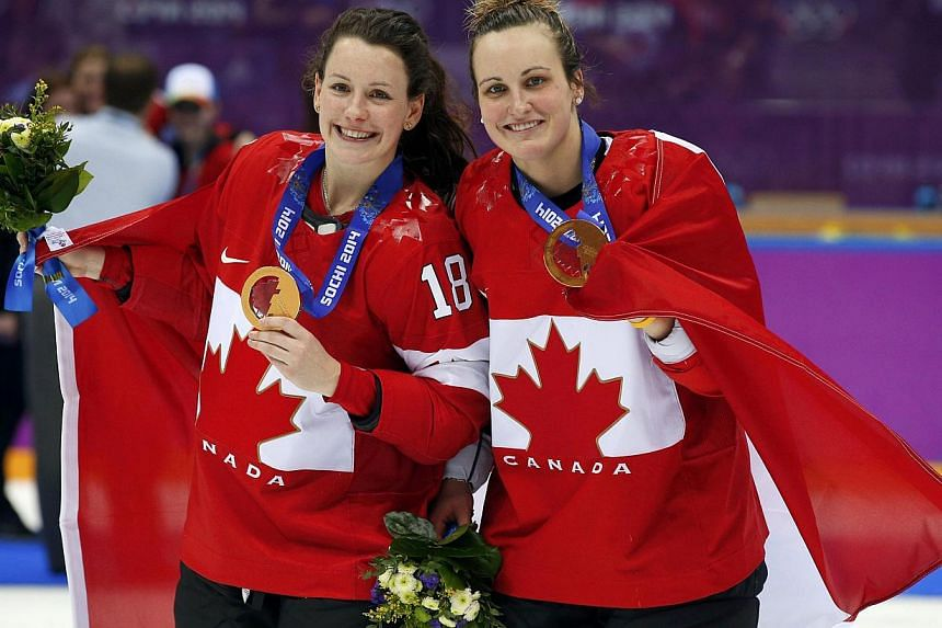 Gold medallists Canada's Catherine Ward (left) and Marie-Philip Poulin pose after the women's ice hockey gold medal game at the Sochi 2014 Winter Olympic Games on Feb 20, 2014. -- PHOTO: REUTERS