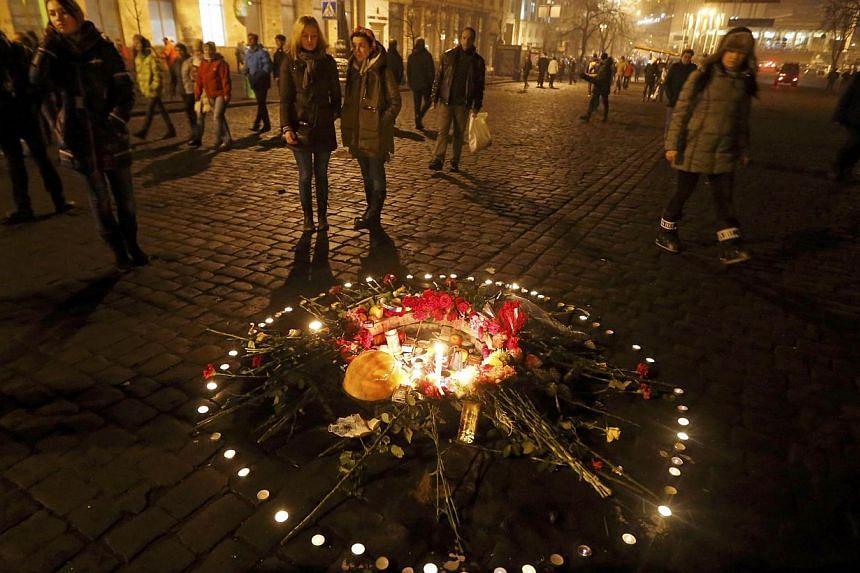 Candles are seen lit on the pavement in the memory of victims of recent violent protests in the Independence Square in Kiev on Feb 21, 2014.Ukraine's embattled leader signed a deal Friday with the opposition in a bid to end the ex-Soviet coun
