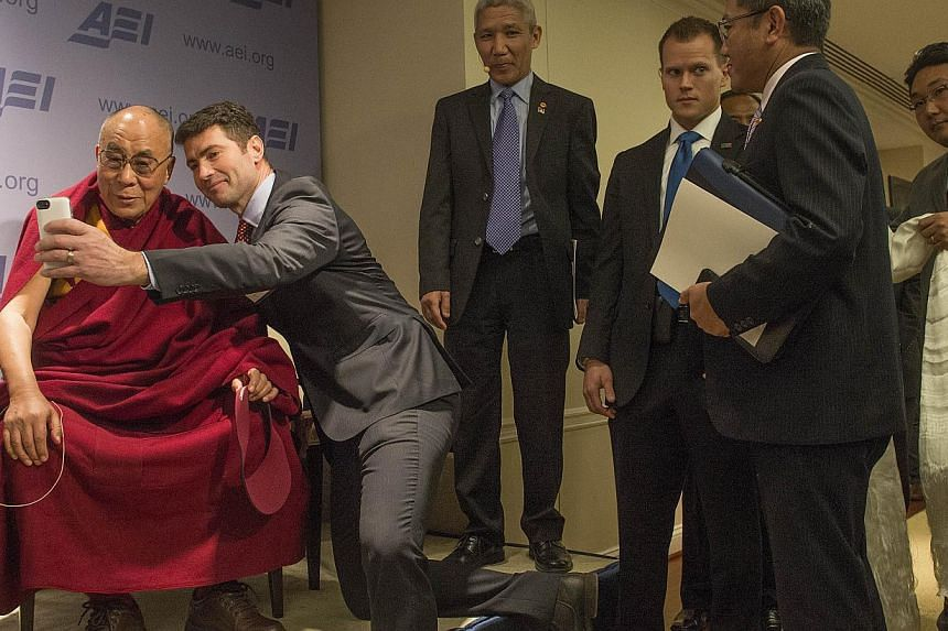 "A member of the audience, Mr Alek Boyd (second from left), takes a photograph with his cell phone of the Dalai Lama (left) at the American Enterprise Institute (AEI) during a panel discussion on ""Happiness, Free Enterprise, and Human Flourishing"" in"