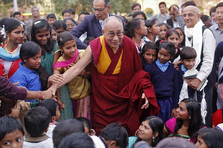 Exiled Tibetan spiritual leader the Dalai Lama poses for a picture along with street children adopted by a charitable day-boarding school in New Delhi last year. -- PHOTO: REUTERS
