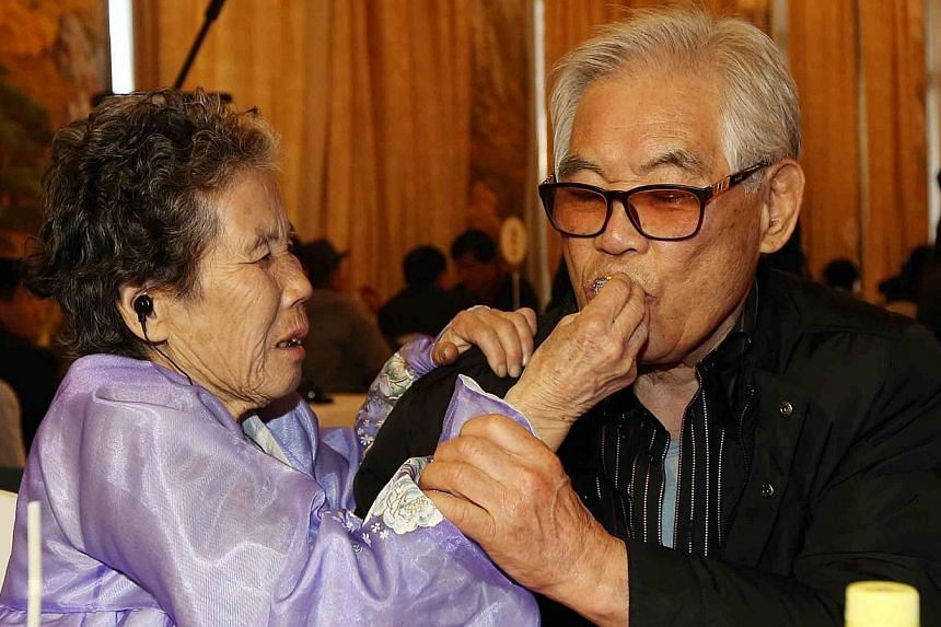 Kim Bong Hak (right) of South Korea is fed by his sister Kim Pong Oak of North Korea during a meeting at a venue in North Korean resort area of Mount Kumgang on the second day of family reunions between North and South Korea on Feb 21, 2014. -- PHOTO