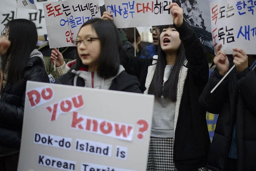 Demonstrators hold placards and shout slogans during a protest over the disputed Dokdo islands in front of the Japanese Embassy in Seoul on February 22, 2014. Japan is holding its annual 'Takeshima Day' commemorating the Takeshima Islands, currently