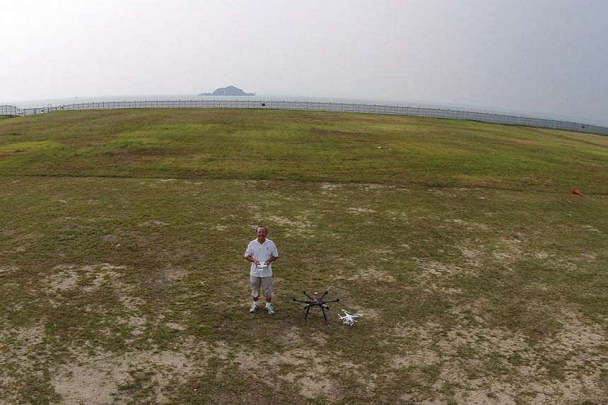 Mr Ronald Yong operating one of his multi-rotor copters on an open field in Tuas, and a photo (above) of himself taken by the drone. The camera is controlled by a smartphone app. -- ST PHOTO: MARK CHEONG