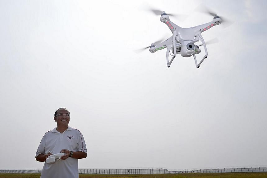 Mr Ronald Yong (above) operating one of his multi-rotor copters on an open field in Tuas, and a photo of himself taken by the drone. The camera is controlled by a smartphone app. -- ST PHOTO: MARK CHEONG