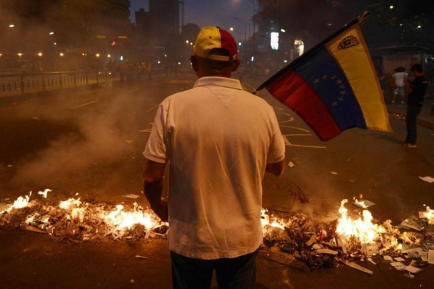 A man holds a Venezuelan national flag next to a barricade during an anti-government demo, in Caracas on Feb 21, 2014. The death toll from escalating anti-government protests in Venezuela jumped to eight on Friday, as President Nicolas Maduro's lefti