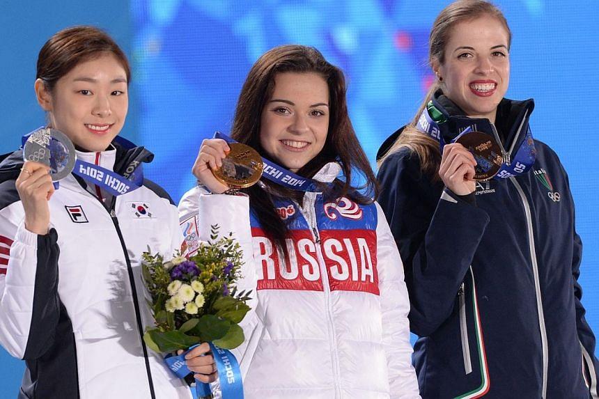 South Korea's silver medallist Kim Yuna, Russia's gold medallist Adelina Sotnikova and Italy's bronze medalist Carolina Kostner (left to right) pose during the Women's Figure Skating Medal Ceremony at the Sochi medals plaza during the Sochi Winter Ol