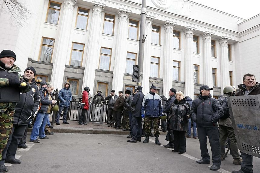 Anti-government protesters guard the entrance to the Ukrainian Parliament building in Kiev, Feb 22, 2014.Ukraine's opposition pressed for the resignation of President Viktor Yanukovich on Saturday, Feb 22, 2014, in the wake of a deal to end day