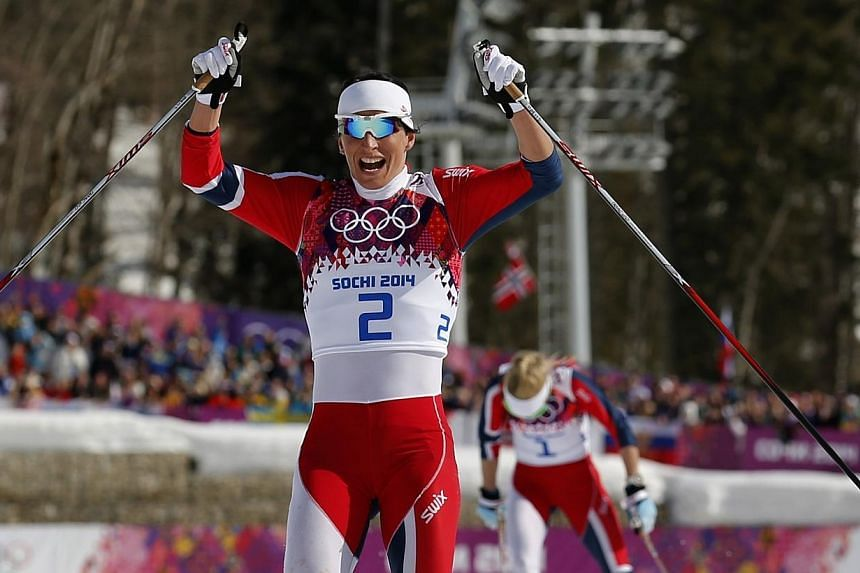 Norway's Marit Bjoergen celebrates as she crosses the finish line ahead of compatriot Therese Johaug to win the women's cross-country 30 km mass start free event at the Sochi 2014 Winter Olympic Games, Feb 22, 2014. Bjoergen on Saturday, Feb 22,